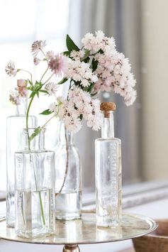 Simple wildflowers in glass bottles enhance the cottage mood.