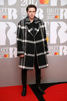 Arriving at the BRITs yesterday evening, Brooklyn Beckham is pictured wearing Burberry outerwear on the red carpet