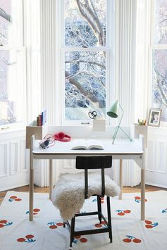 White walls, sheep skin, black chair, white desk, green desk lamp,.