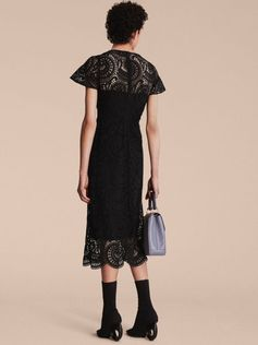 A shift dress crafted in swirled macramé lace, forming a scalloped edge at the hem. Flared sleeves are fixed to the fitted body to create a flattering, feminine silhouette.