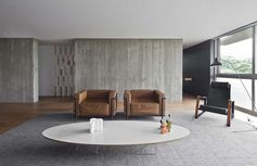 Concrete walls are warmed up by rich leather chairs.
