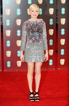 "Michelle Williams wearing Louis Vuitton to the 70th EE British Academy Film Awards (BAFTA) where she was nominated for ""Best Actress in a Supporting Role"" for Manchester by the Sea. She is wearing a custom embroidered dress, velvet sandals and Louis Vuitton high jewelry ring."