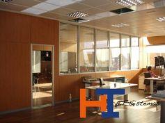 Mampara de oficina, modelo Milán, formado por zócalo inferior de tablero plastificado con altura variable y resto a techo en doble cristal montado sobre cerco de aluminio.