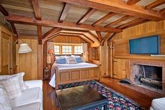 The wood paneling and exposed beams (and fireplace! Oh, the fireplace!) in this nautical bedroom is simply wonderful.