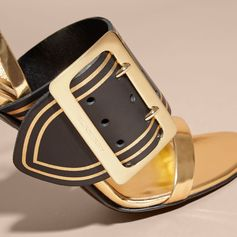 Smooth leather two-tone sandals offset with an oversize polished gold-tone metal buckle in homage to our trench coat. The sleek design is finished with a buckled ankle strap and a stiletto heel.