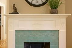 White wood mantle and blue tile surround.