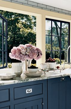 Open windows, fresh air and lavender hydrangeas complement blue-gray kitchen cabinets in Ralph Lauren Paint Rue Royale