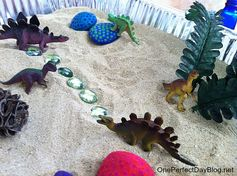 Painted rocks dinosaur game.  Fill aluminum disposable tray with sand, bury eggs and decorate surface.  Great for kids play or Toddler Dinosaur Party.