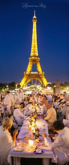 Diner en Blanc, also known as Diner in White, a top secret invitiation-only flash mob in Paris, France where 11,000 people dressed entirely in white clothes spontaneously set up tables and chairs in front of historic landmarks one night a year. Photographed by Stacy Reeves