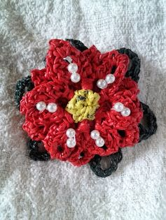 Free Crochet Pattern: Plarn Poinsettia Brooch - Look how beautiful #plarn can become when you put some extra work into it! Although this #poinsettia was created for #winter, this #freecrochetpattern could be created in many different colors for a year-round #accessory.