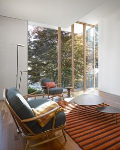 living room with wood chairs and orange rug in a modern Toronto house