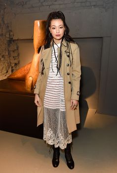 Rina Ohta in a Burberry Trench coat and appliqued jersey with cable knit panels over a panelled dress, crafted from ornate embroidered tulle, with decorative scalloped trims and a Breton striped top.