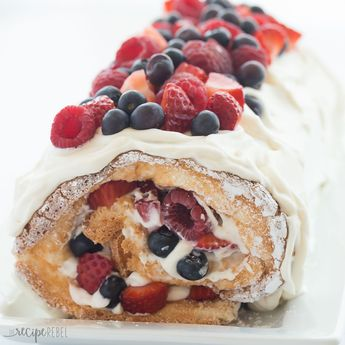This Triple Berry Angel Food Cake Roll is an easy red, white and blue dessert (or just red and white!) for the 4th of July or Canada Day, or any day! Perfect with fresh summer strawberries, raspberries and blueberries Includes step by step recipe video. #video #recipe #recipevideo #cake #dessert #strawberry #blueberry #raspberry