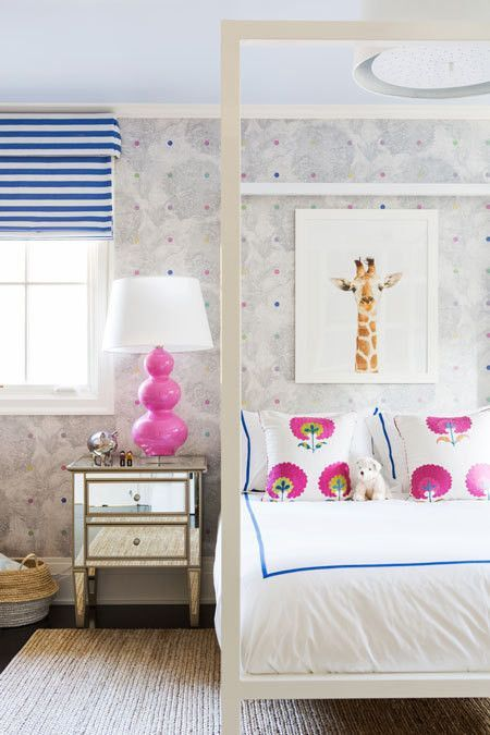 Blue-and-white striped Roman shades and a hot pink bedside bring bright hues to a cheerful girls room.