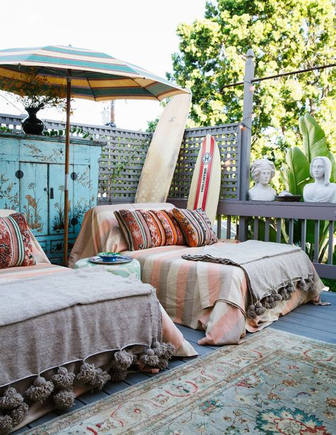 Two outdoor chaises are draped for lounging under a vintage striped beach umbrella.