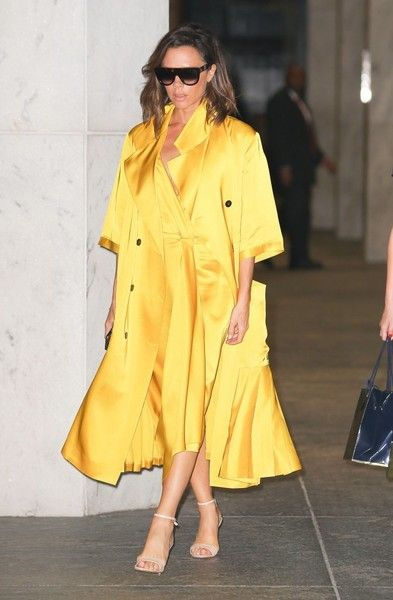 Fashion designer Victoria Beckham is seen leaving an office building in New York City, New York on June 23, 2016. Victoria was wearing a bright yellow jacket to match her bright yellow dress.