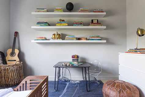 Miniature Lucite chairs gather around a child-sized desk, situated beneath floating shelves.