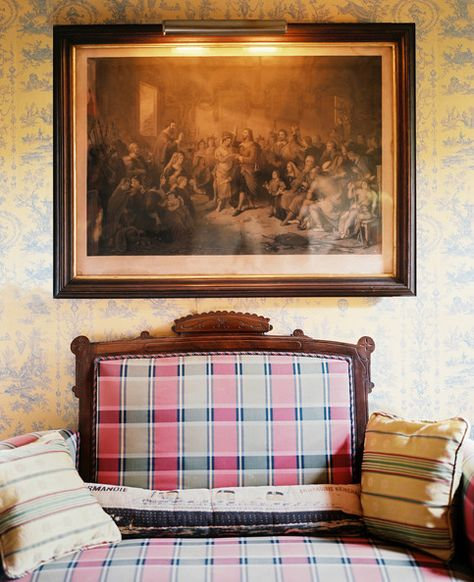 Decorating With Plaid: An understated toile de jouy wallpaper and serious artwork preside over a wide armchair upholstered in a handsomely faded tartan.