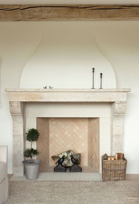 Contrasting herringbone stonework offsets an aged white mantel in the living room.