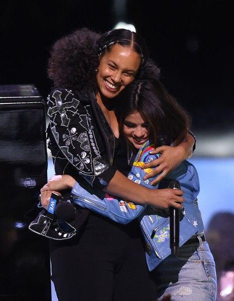 Alicia Keys (L) and Selena Gomez appear on stage at WE Day California.