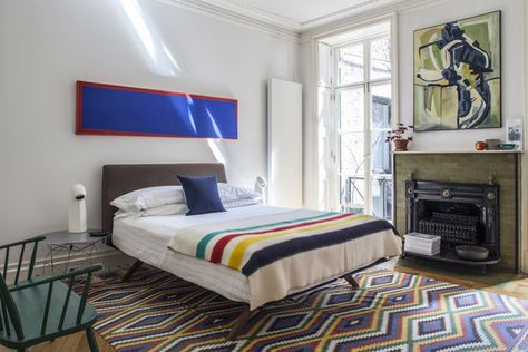 Traditional Fireplace: A midcentury-inspired bed topped with a striped wool blanket.