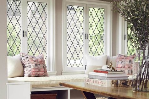 The cheerful window seat was original to the home, made current by custom cushions in contemporary and vintage fabrics. The rattan poufs are from Lawson-Fenning and the sofa table – once her dining table in New York City – was an eBay purchase.