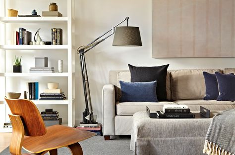 "Approachable furnishings from retail stores such as West Elm were paired with custom-made items, including a linen-upholstered ottoman and wool rug, for a ""one-of-a-kind"" look."