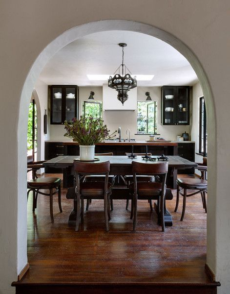 A Spanish-Style Compound for Indoor-Outdoor Living in L.A.: An arched doorway gives way to a 1920s dining table.