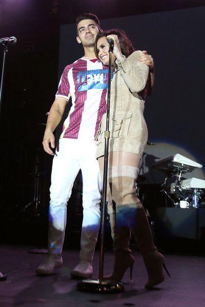 Recording artists Joe Jonas and Demi Lovato hug onstage during the LA Demi Lovato and DNCE Concert.