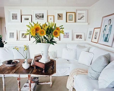 The Best Beach Houses Around the World: A spacious and cozy white sectional sofa is surrounded by shelves of leaning framed artwork.