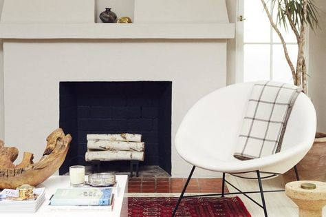 Farrow & Ball's Elephant's Breath was painted on the plaster hearth, with a chic pop of black on the interior. In front, a vintage half moon chair is arranged beside a cork stool from Hive Modern.