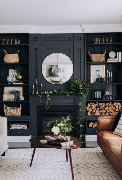Black panelled walls in living room with fire place and built ins