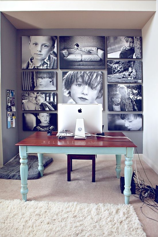 An entire wall of black and white poster pictures on a gray wall. Future office