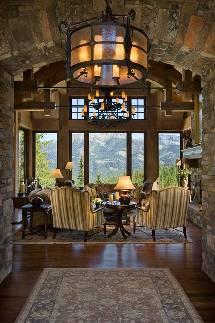 Magnificent rustic great room with a stone archway and massive windows with a breathtaking mountain view