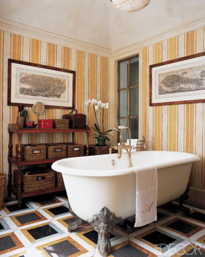 In a marble-floored master bath designed by Laura Sartori Rimini and Roberto Peregalli, 18th-century engravings hang against striped wallpaper.