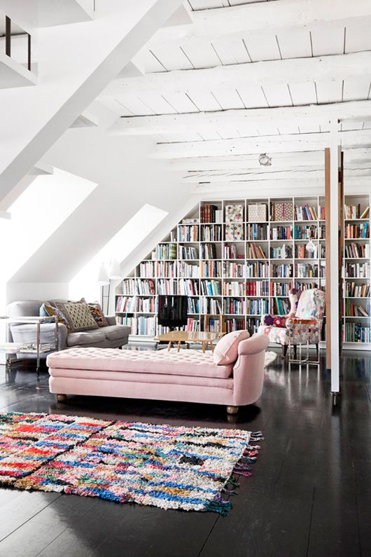 general: dark floors with white walls and ceilings pop of color furniture and rug colorful bookshelf