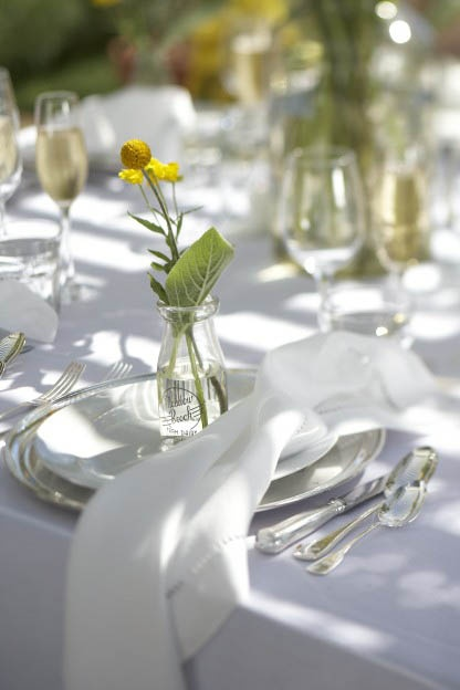 Blooms in old-fashioned bottles work as flower arrangements and party favors in one