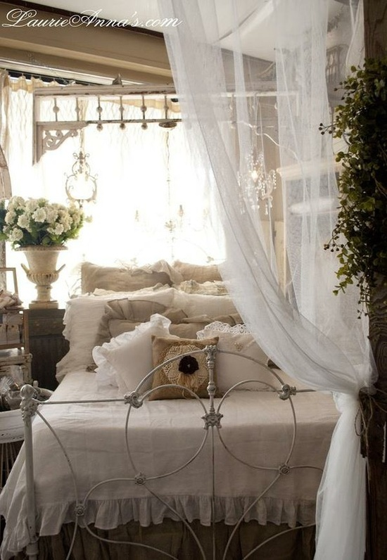 """White ornate iron bed, white spread with sheer 6"""" ruffle, assortment of neutral ruffle pillows, white urn with white hydrangea, white Victorian wood beadwork hanging over bed,  sheer drape to divide bedroom pulled back and tied at entry, charming vintage"""