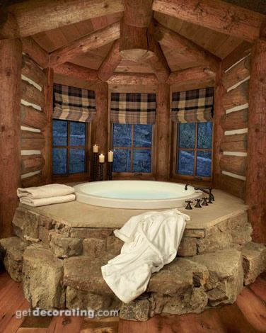 Log home bath....rock surrounds the round bath