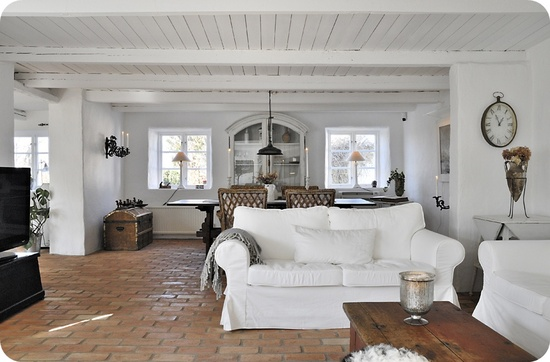 Brick floor, white walls and couches