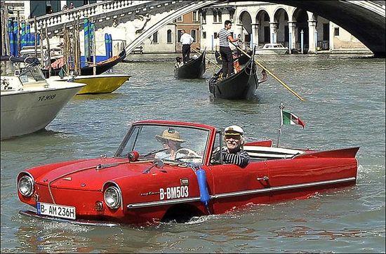 Amphicar passes gondoliers as he goes under the Rialto Bridge