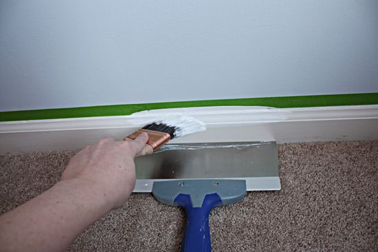 Paint trim without it getting on the carpet. A dust pan works nicely, too.