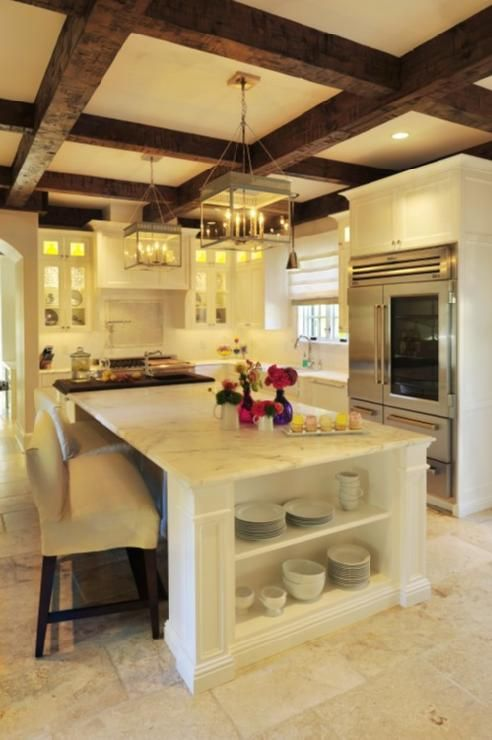 Beckwith Interiors    Beautiful rustic kitchen design with exposed wood beams, gray square kitchen island lanterns, creamy white glass-front shaker kitchen cabinets, white kitchen island, calcutta gold counter tops and farmhouse sink.