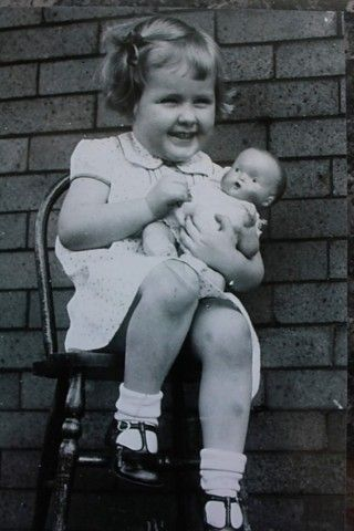 Vintage photo a little girl with her favorite doll, circa 1940.