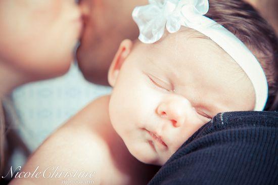 Beautiful Baby Newborn Photo with parents kissing        Nicole Christine Photography
