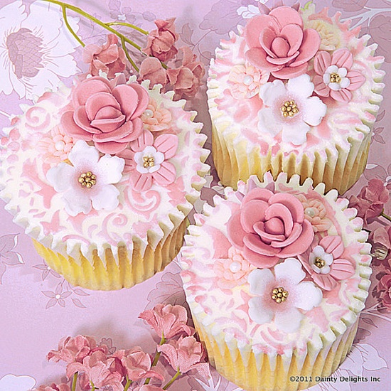 delicious vanilla cupcakes or cookies frosted in white icing and embellished with dusty pink stencil designs and further adorned with white flowers with edible mini gold pearls, pink roses and pink flowers with white centers.