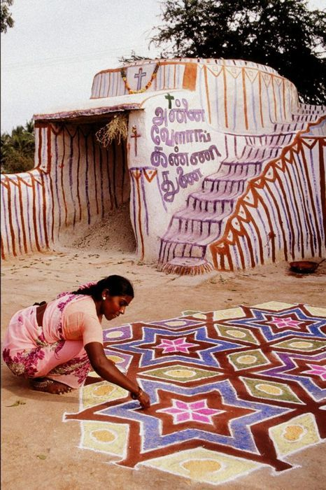 A woman painting a kolam in Tamil Nadu, India. A kolam is a form of sandpainting that is drawn using rice powder by female members of the family in front of their home.