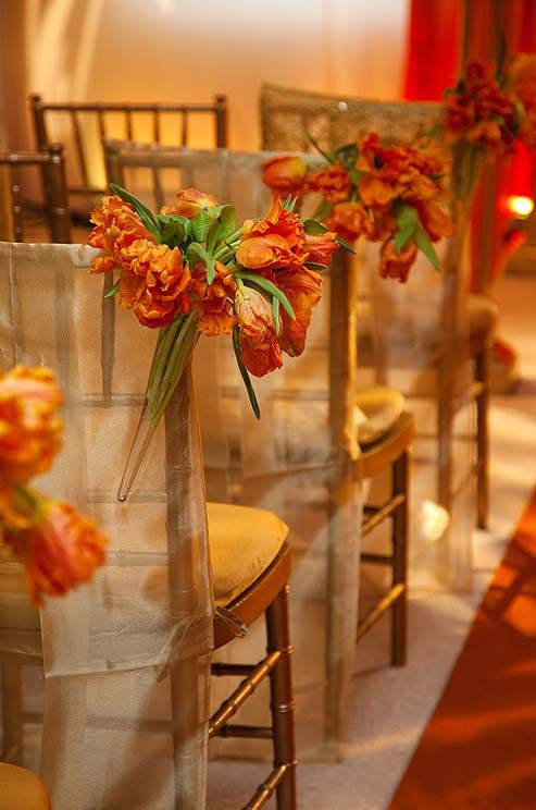 Bouquets of orange parrot tulips lined the aisle.