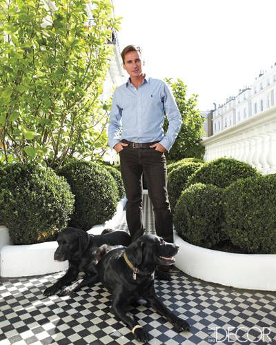 Interior designer Peter Mikic with his black Labradors, Hunter and Bullitt, in the front garden of his Notting Hill home.