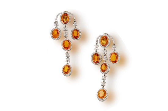 A pair of orange sapphire and diamond pendant earclips each designed as a cascade of five oval-shaped orange sapphire and round brilliant-cut diamond clusters, with further round brilliant-cut diamond detail; estimated total orange sapphire weight: 30.00 carats; estimated total diamond weight: 7.95 carats; mounted in eighteen karat white gold; length: 2 3/4in.